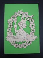 Rabbit with carrot in a wreath of flowers